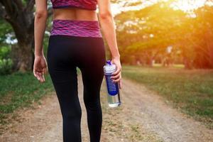 ein weiblicher Läufer, der draußen steht und eine Wasserflasche hält, gesundes und Sportkonzept
