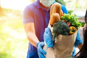 Foodservice-Anbieter mit Masken und Handschuhen. Zu Hause bleiben reduziert die Ausbreitung des Covid-19-Virus