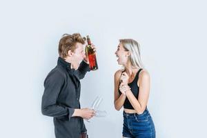 Porträt des glücklichen jungen Paares, das Wein im Studio trinkt