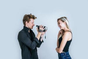 glückliches Porträt des Paares, das Videokamera hält und ein Video aufzeichnet foto