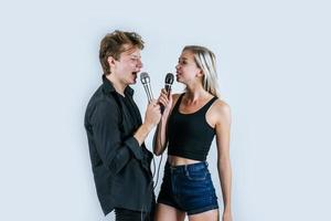 glückliches Porträt des Paares, das Mikrofone hält und singt