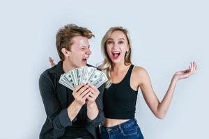 glückliches Paar, das Dollarbanknoten zeigt