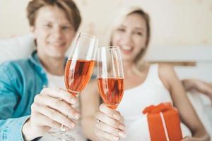 glückliches Paar, das Wein im Schlafzimmer trinkt
