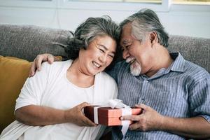 älteres Ehepaar überrascht mit Geschenkbox im Wohnzimmer
