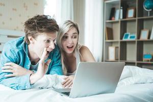 glückliches Paar mit Laptop auf dem Bett