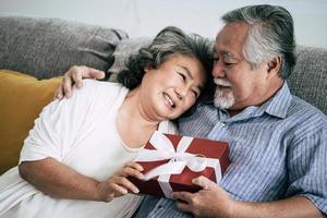 älteres Ehepaar überrascht mit Geschenkbox im Wohnzimmer foto