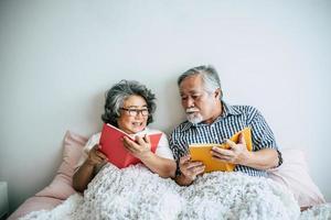 älteres Ehepaar, das auf dem Bett liegt und ein Buch liest