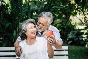 älteres Ehepaar, das etwas Obst spielt und isst