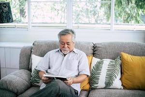 alter Mann liest im Wohnzimmer