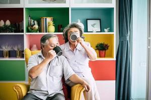 älteres Ehepaar, das zusammen spricht und Kaffee oder Milch trinkt