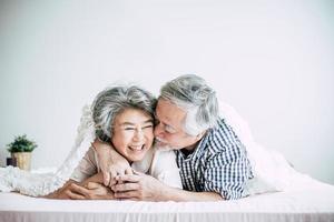 glückliches älteres Paar, das im Schlafzimmer lacht
