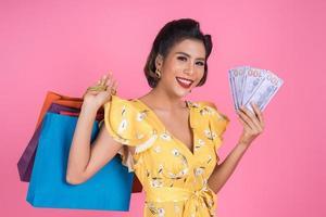 glückliche f modische Frau, die Geld für das Einkaufen hält