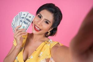 glückliche modische Frau, die Geld hält