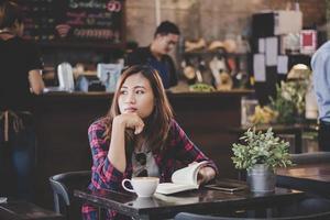 glückliche Geschäftsfrau, die ein Buch liest, während sie im Café entspannt