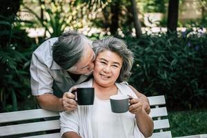 ältere Paare spielen und trinken Kaffee