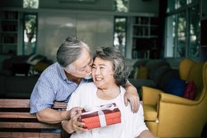 lächelnder älterer Ehemann, der Überraschung macht und seiner Frau Geschenkbox gibt foto