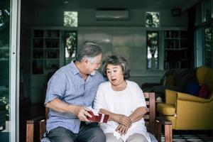 lächelnder älterer Ehemann, der Überraschung macht und seiner Frau Geschenkbox gibt