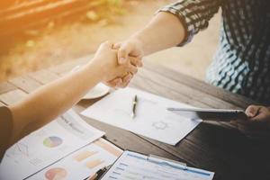 Nahaufnahme von zwei Geschäftsleuten, die Hände schütteln, während sie am Arbeitsplatz sitzen foto