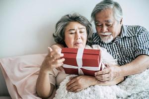 lächelnder älterer Ehemann, der Überraschung macht und seiner Frau im Schlafzimmer Geschenkbox gibt