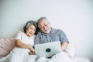 älteres Ehepaar spricht und benutzt Laptop im Schlafzimmer