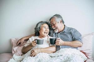 älteres Paar lacht beim Kaffeetrinken im Schlafzimmer