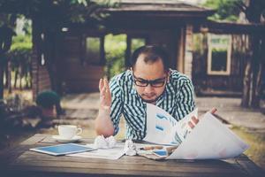 gestresster Geschäftsmann mit Papieren und Diagrammen, die zu Hause am Tisch sitzen foto