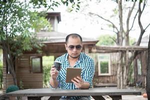 junger Mann sitzt draußen an einem Holztisch und entspannt mit Tablette foto
