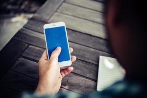 Nahaufnahme des Geschäftsmannes mit Smartphone während der Arbeit im Café foto