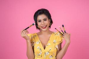 Porträt einer Frau mit Make-up Pinsel foto