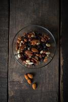 gemischte Nüsse, die aus einer Schüssel auf hölzernem Hintergrund gießen