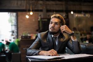hübscher Geschäftsmann, der an Arbeit während der Arbeit im Café denkt foto