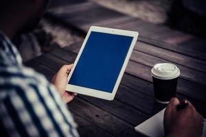 junger Mann, der digitale Tablette beim Kaffeetrinken im Hausgarten verwendet foto