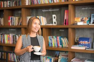 asiatische Frau, die mit Kaffee im Café entspannt foto