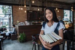 lächelnde junge Frau, die Bücher hält foto