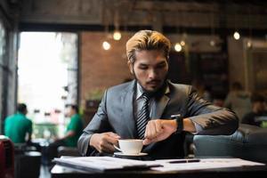 Geschäftsmann, der auf seine Uhr schaut, während er im Café arbeitet foto