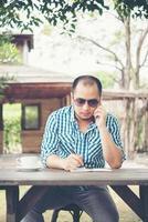junger Geschäftsmann, der Smartphone während der Arbeit im Hausgarten verwendet foto