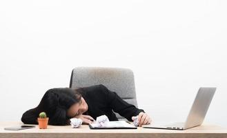 müde überarbeitete junge Geschäftsfrau schläft im Büro am Arbeitsplatz foto