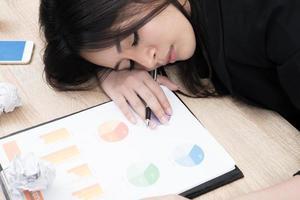 müde überarbeitete junge Geschäftsfrau schlafen im Büro foto