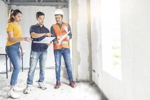 junge asiatische Ingenieure bauen ein Haus