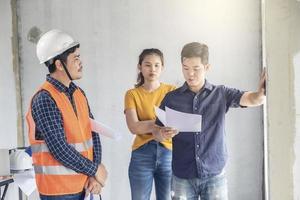 junge asiatische Ingenieure bauen ein Haus foto