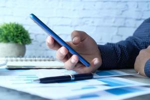 Person, die ein blaues Mobiltelefon benutzt