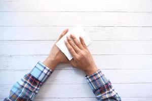 Mann desinfiziert Hände mit einem feuchten Tuch foto