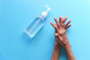 Person, die Händedesinfektionsmittel auf einem blauen Hintergrund verwendet foto