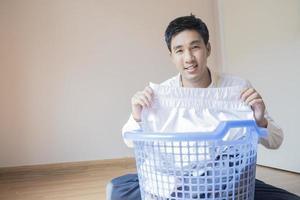 asiatischer Mann, der Wäsche faltet foto