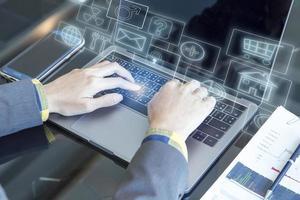 Frau, die einen Computer mit schwebenden Symbolen benutzt foto