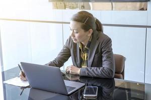 Geschäftsfrau, die an einem Laptop arbeitet foto