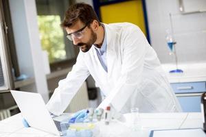 Forscher im weißen Laborkittel, der mit Laptop arbeitet, während er im Labor sitzt foto