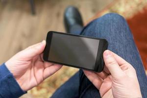 Nahaufnahme eines Mannes, der ein mobiles Smartphone hält foto