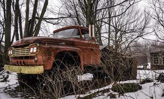 rostiger Weinlese-Ford-Lastwagen unter Bäumen in einem verschneiten Hof foto