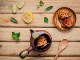 Teekanne mit frischen Kräutern auf einem Holztisch foto
